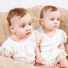 Two adorable baby twins sitting in the chair.