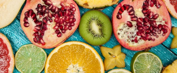 Colorful fruit slices on blue wood surface