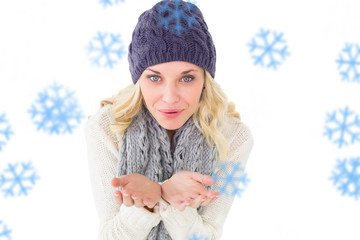 Pretty blonde in winter fashion blowing over hands against snowflakes