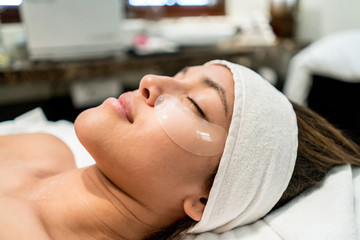 Latin american woman at a beauty treatment with gel pads under her eyes relaxing
