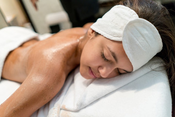 Pretty latin american woman at the spa lying down after a back massage with oil