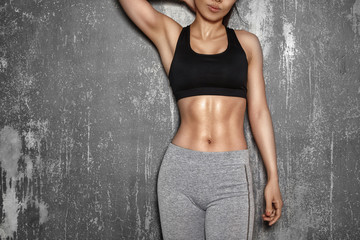 Fit Woman style with sexy hips. Female with perfect abdomen muscles. Beautiful Body in sport clothes near grey wall Fototapete