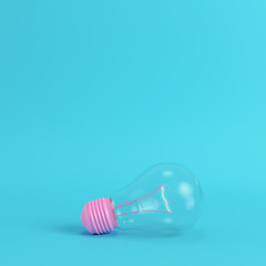 Pink light bulb on bright blue background in pastel colors. Minimalism concept