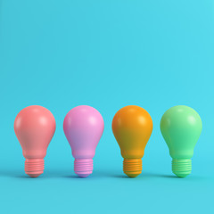 Colorful light bulbs on bright blue background in pastel colors