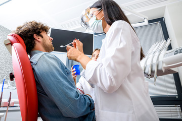 A female Dentist preparing to examine a Patient