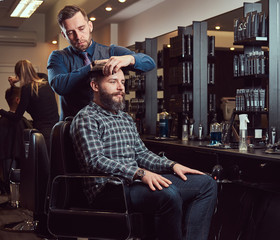 A stylish Master barber does a haircut to the client. Men's haircut in a barbershop.