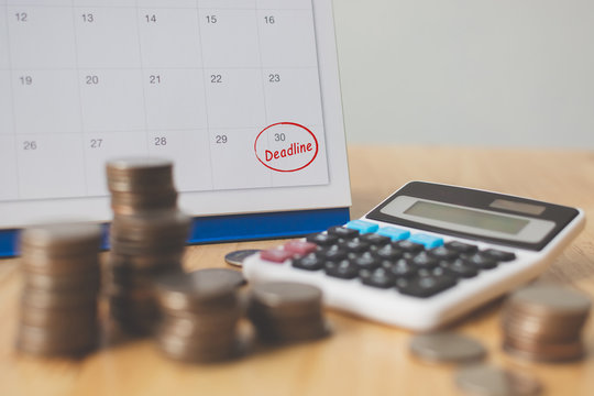 Tax payment season and finance debt collection deadline concept. Money coins stack, calendar and calculator