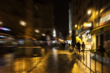 Blurry motion image of people walking on street at night in Paris.