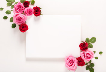 Roses and blank greeting card top view flat lay