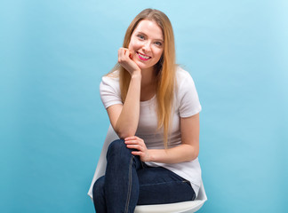 Portrait of a young woman sitting in a chair against a solid color background