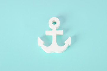 White wooden Anchor model on blue background - Nautical background