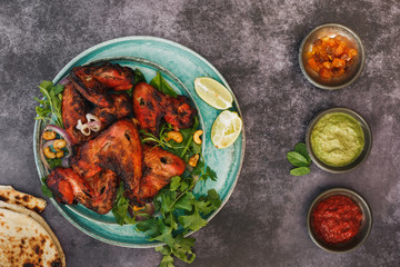 Spicy tandoori chicken wings served with  traditional assortment of sauces on rustic table, top view