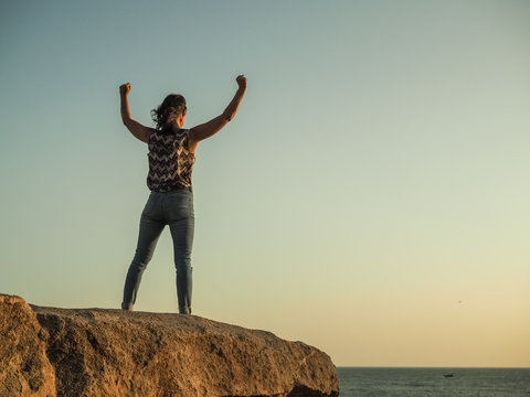triumphant WOMAN IN YES POSE WITH arms wide open on top of a rock at the beach