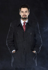Portrait of fashionable well dressed man with beard posing outdoors looking away, confident and focused mature man in coat standing  on a black background, elegant fashion model.
