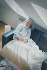 Sick mature woman sitting on sofa at home under blanket