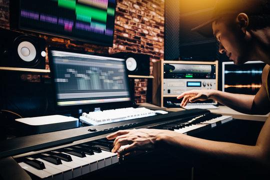 asian male music arranger hands composing song on midi piano & professional audio equipment in digital recording studio
