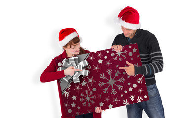 Couple holding a white sign against christmas wrapping paper with bow