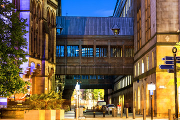 Illuminated old historical buildings in the city center of Manchester, UK at night