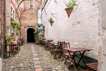 Small outdoor cafe in old style narrow street with brick walls, wooden furniture and cobbled stones.