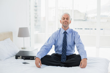 Relaxed businessman sitting with eyes closed on bed