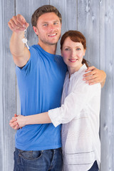 Couple holding keys to home against bleached wooden planks background