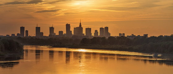 Evening panorama of Warsaw skyline over Vistula river at sunset, Poland
