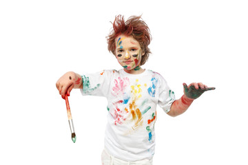 Young emotional boy with brush, his face and hands painted with paints, vivid emotions, messy hair