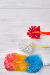 Set of brushes for house cleaning. Plastic toilet brushes, copy space. Fluffy colorful duster. Home cleaning supplies.