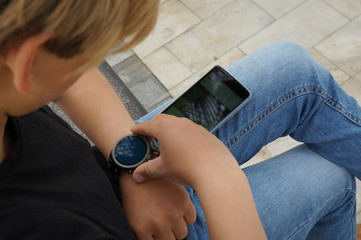 Teenager connecting his smartwatch with his smartphone