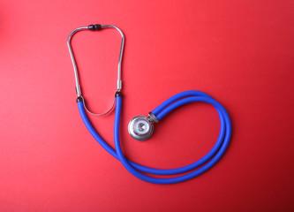 Medical blue stethoscope isolated on red background