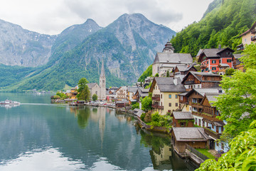 Scenic picture-postcard view of famous Hallstatt mountain village in the Austrian Alps with passenger ship in beautiful morning light at sunrise on a sunny day in summer, Salzkammergut region, Austria