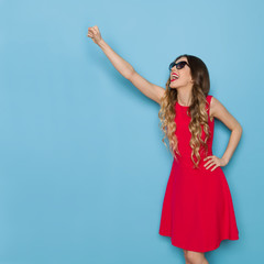 Beautiful Young Woman In Red Dress Is Standing With Fist Raised And Shouting