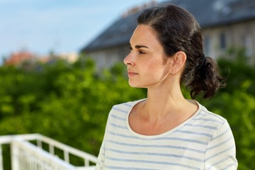 Woman on balcony, looking away daydreaming