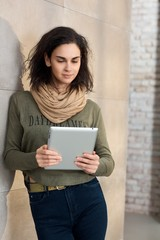Smiling brunette woman using digital tablet