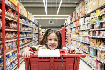 Little girl for a walk in the supermarket