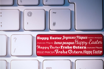 Happy easter in different languages against red key on keyboard
