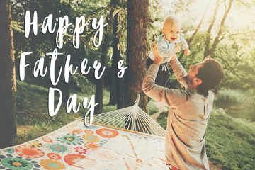 happy father's day text, greeting card concept. Happy hipster father playing with his son in a park near a hammock, family concept, man holding baby outdoors. fathers day