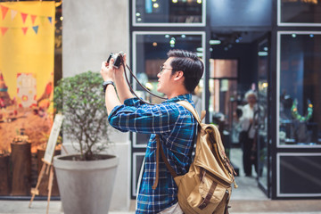 Man travel concept tourist taking photo by phone and put up hand overhead to shoot street and city.