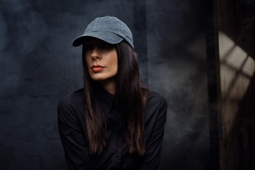 Woman in black wearing black baseball cap