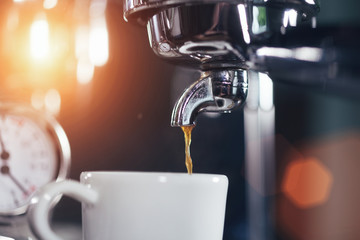 Espresso out of classic coffee machine into coffee cup