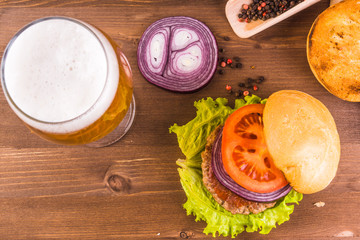 Homemade burger and a glass of beer on a wooden table - top view