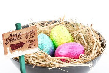 Easter egg hunt sign against foil easter eggs in a bowl