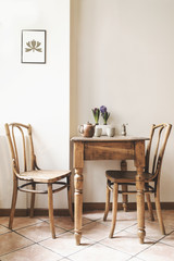 Vintage interior design of kitchen space with small table against white wall with simple chairs and plant decorations. Minimalistic concept of kitchen space.