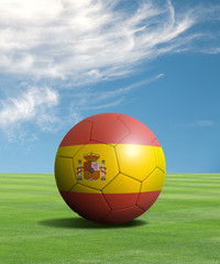 Soccer ball with Spain flags in a green field