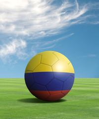 Soccer ball with Colombia flags in a green field