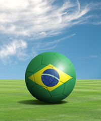 Soccer ball with Brazil flags in a green field