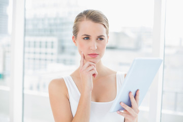 Pensive sporty woman using tablet computer