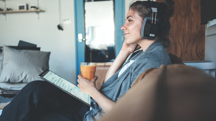 Young nice woman reading tablet pc and listening music, cozy studio apartment