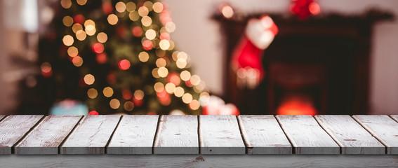 Wooden desk against close up of christmas lights