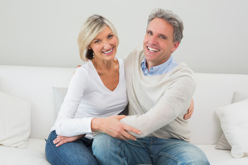 Happy couple embracing on sofa in living room